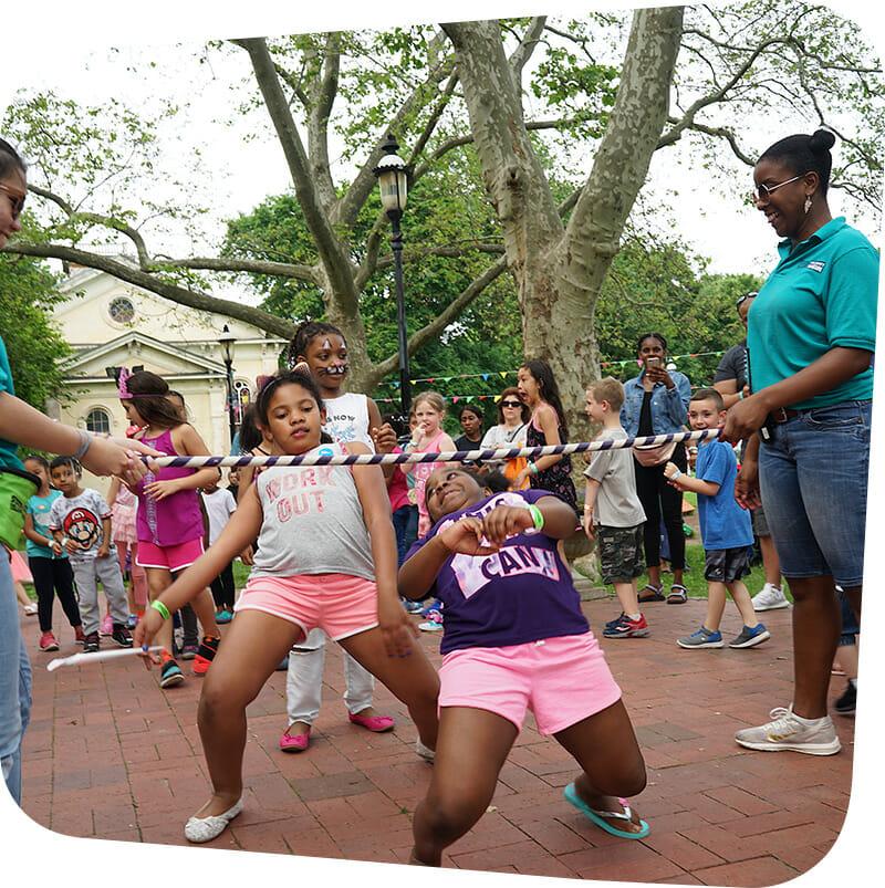 Children going under limbo stick during museum carnival