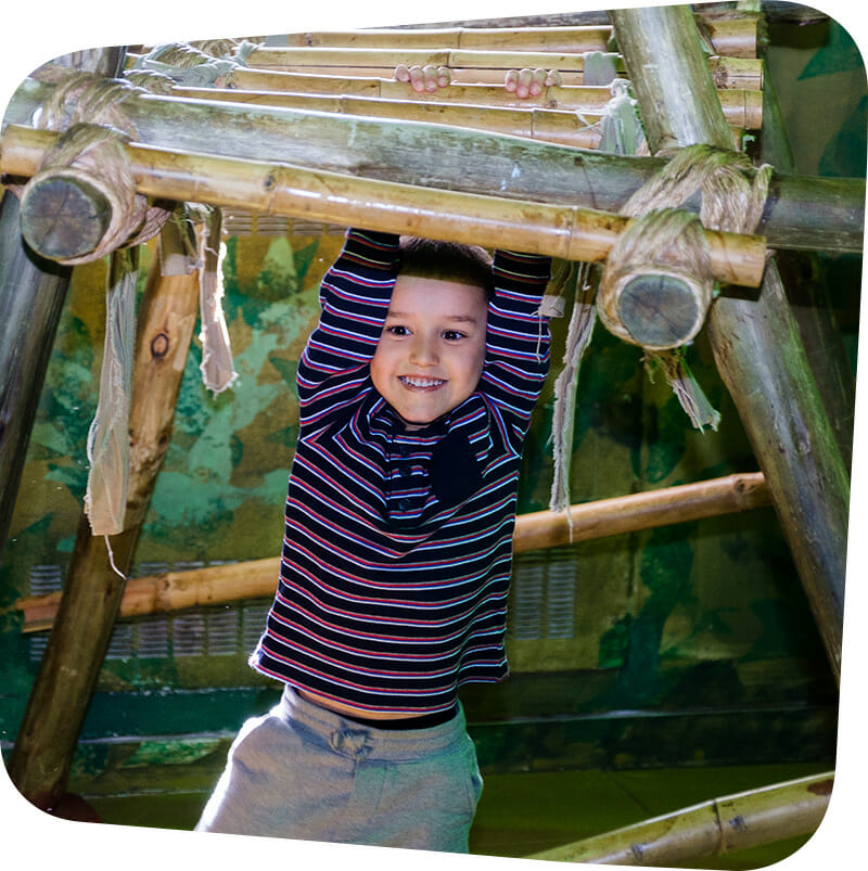 child hanging from bamboo bars in Great Explorations exhibit.