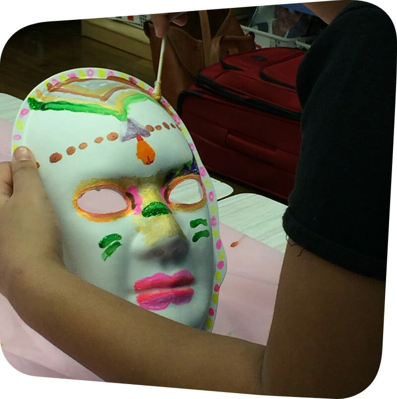 child painting colorful mask