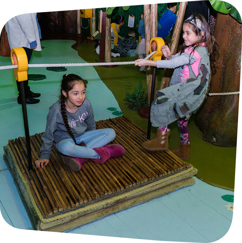 child pulling raft across river in Great Explorations exhibit