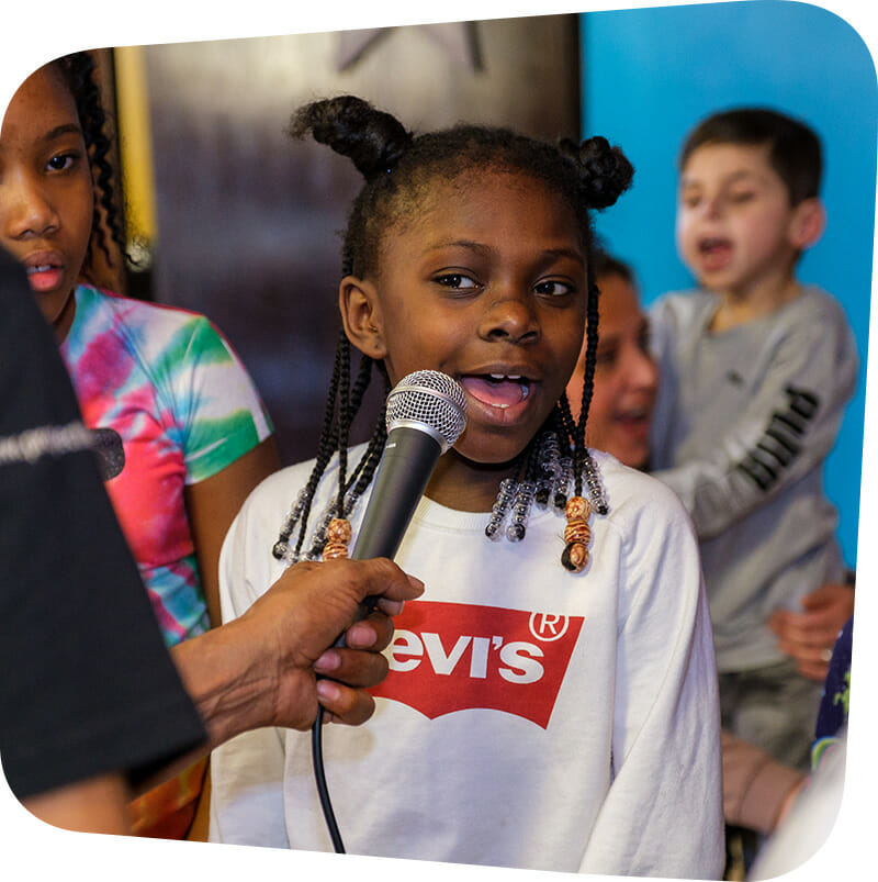 Child speaking into microphone.