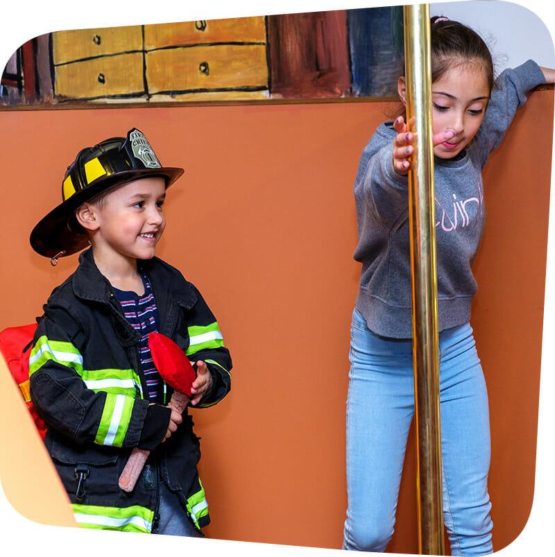 Children playing in firefighter exhibit in firefighter gear.