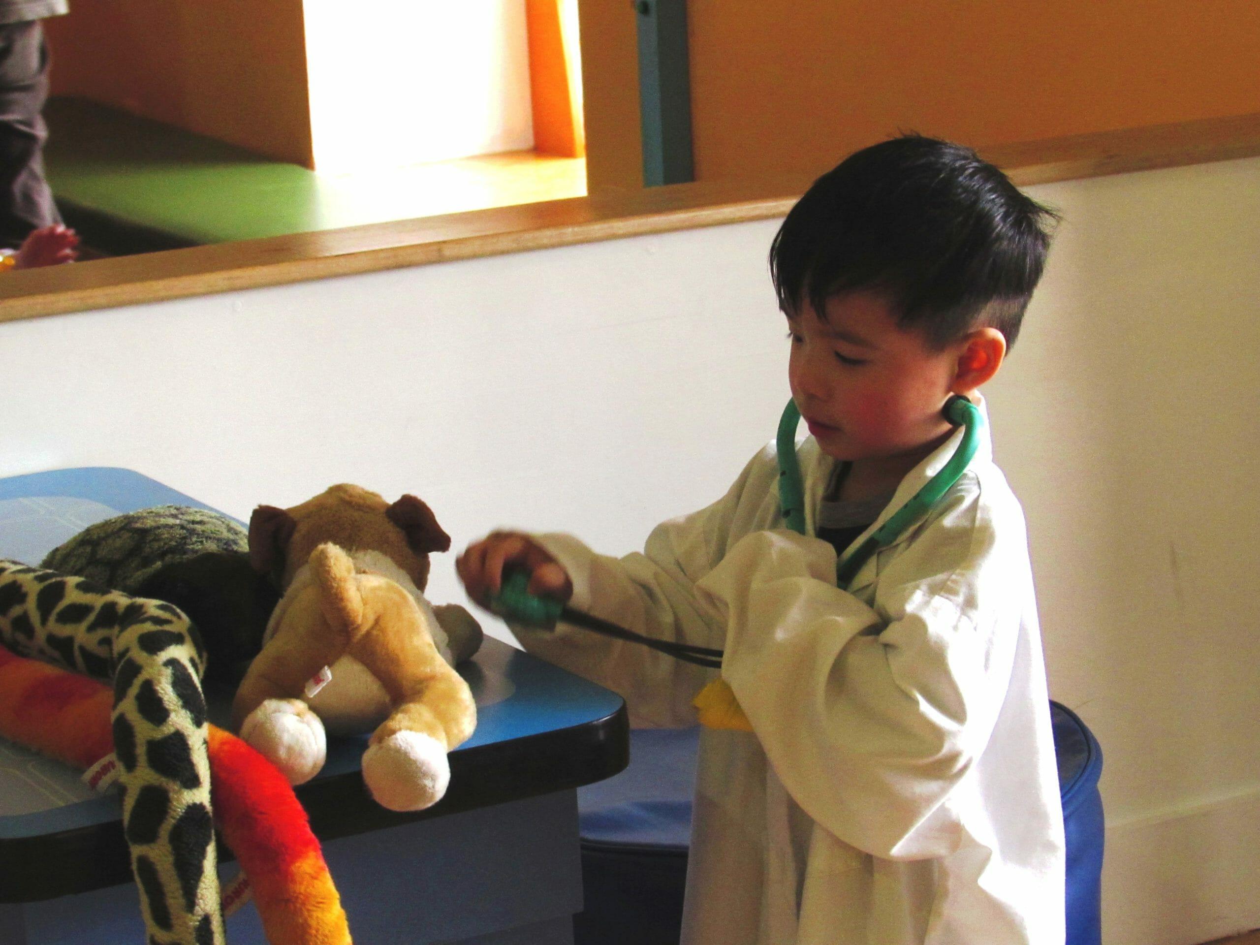 child wearing white doctors coat in vet's office.