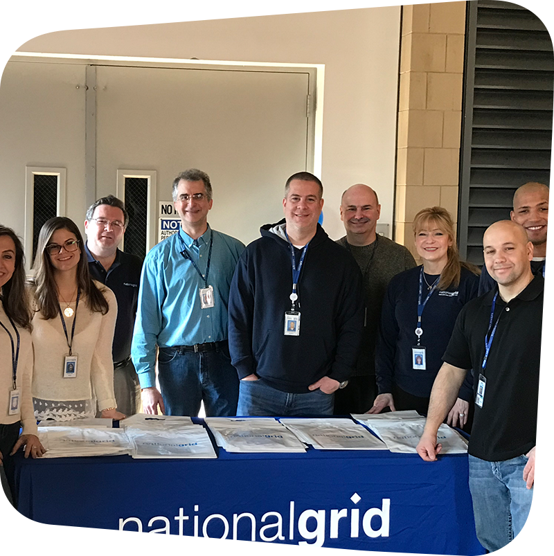 national grid team posing in front of national grid table.