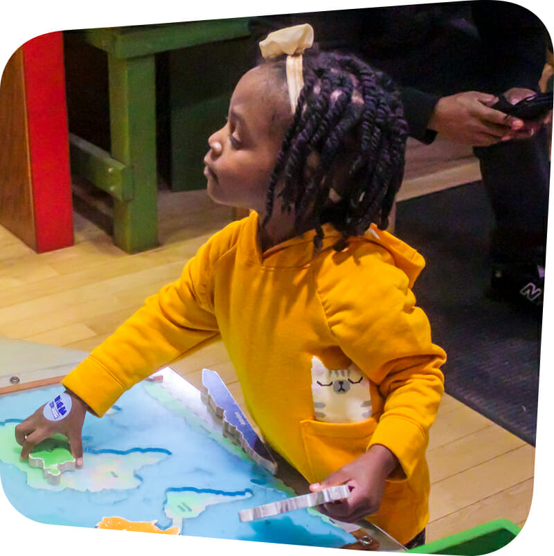 child playing with map in Great Explorations exhibit