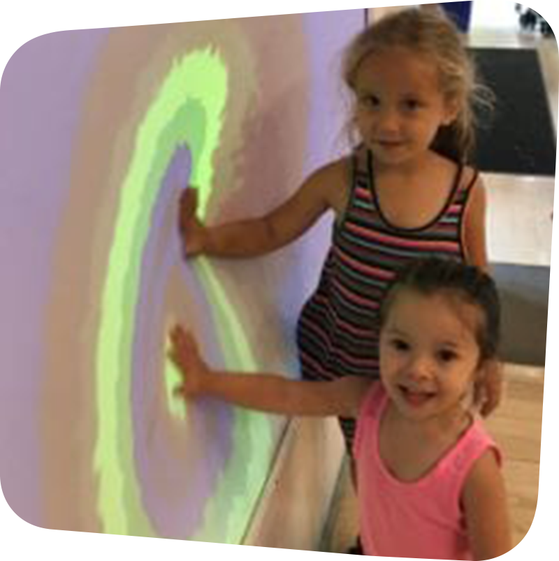 two children touching colorful wall