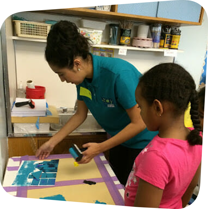 child and staff working on artwork