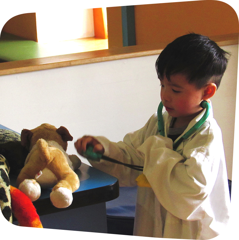 child wearing white doctor coat playing in vet's office