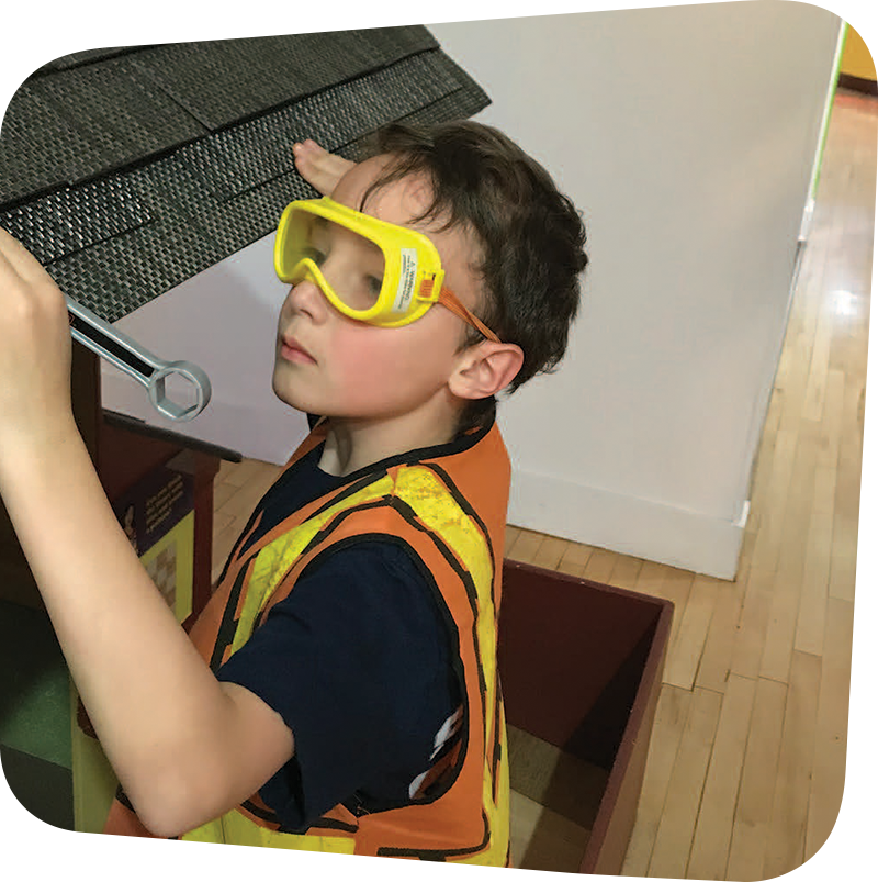 Child with construction goggles and vest playing in House About it Exhibit.
