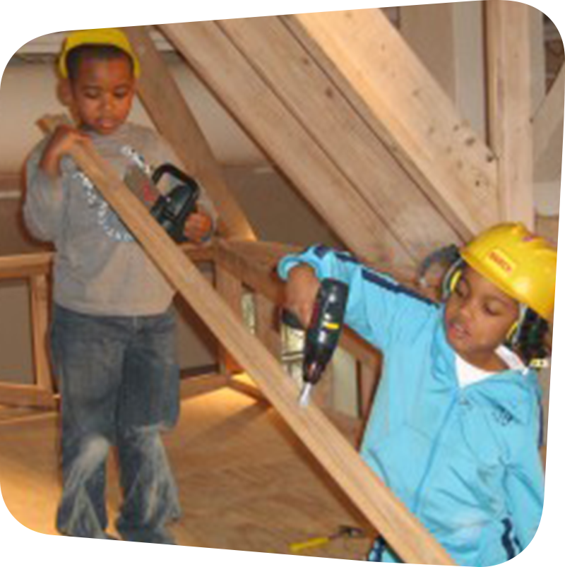 Two children wearing hardhats and playing with tools in House About It exhibit.