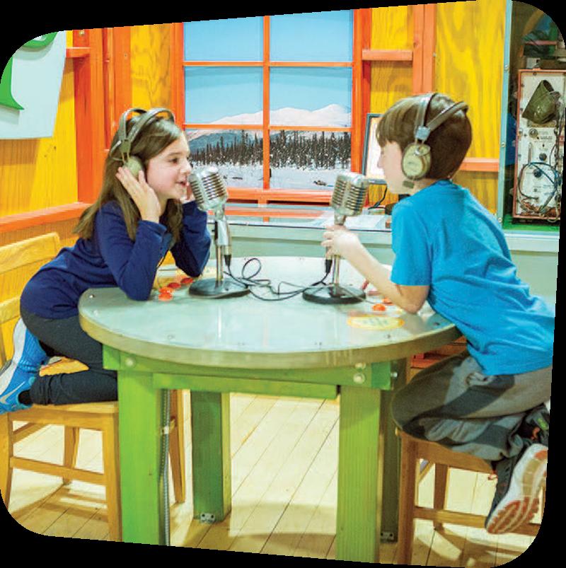 Two children with headphones speaking into microphones.