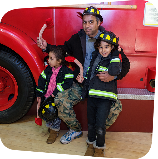 Children posing with parent in front of fire truck while wearing firefighter gear.
