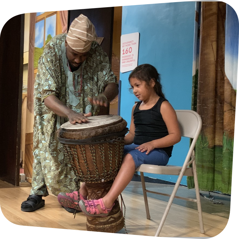 child seated while man plays drums