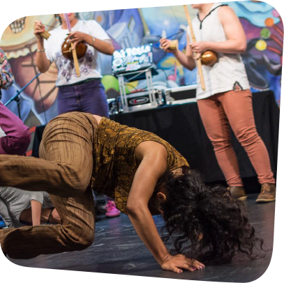 capoeira dancer dancing and people clapping in a circle