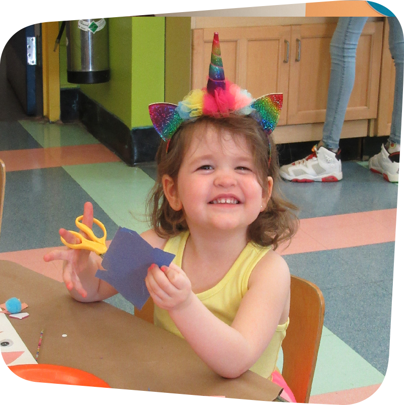 child smiling with art supplies